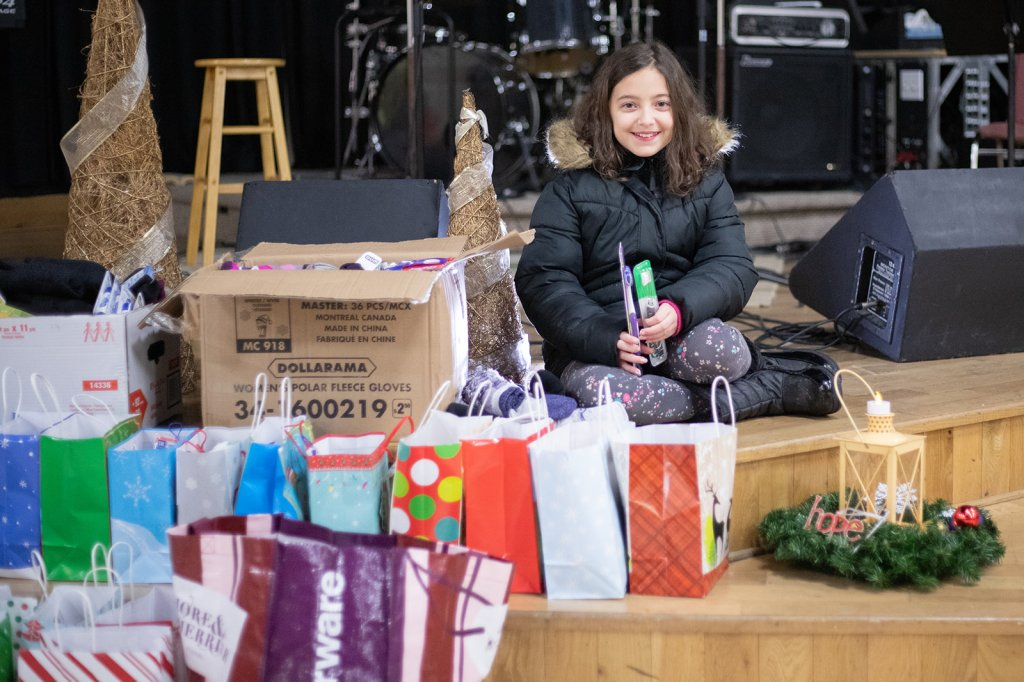 This image shows a young girl with many of the bags and items donated to the Sackville NS Area Warming Centre for the 2019-2020 season. Photograph by Amy Holloway